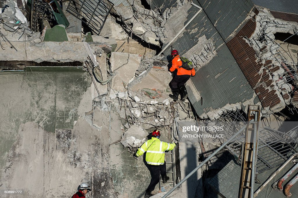 Rescue workers climb to look for survivors in the remains of a building which collapsed in the 6.4 magnitude earthquake, in the southern Taiwanese city of Tainan on February 8, 2016. Rescuers raced on February 7 to free around 120 people buried under the rubble of an apartment complex felled by an earthquake in southern Taiwan that left 34 confirmed dead, as an investigation began into the collapse. AFP PHOTO / ANTHONY WALLACE / AFP / ANTHONY WALLACE