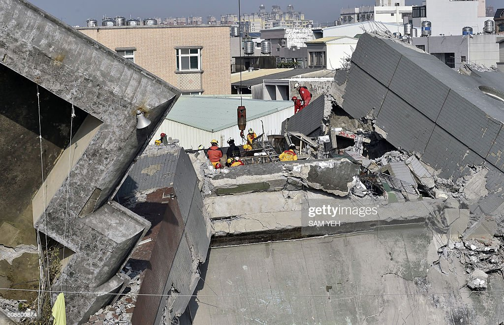 Rescue workers continue the search for survivors at the Wei-kuan apartment complex on the second day of rescue operations following a 6.4 magnitude earthquake in southern Taiwan's city of Tainan on February 7, 2016. Rescuers searched through the night hoping to free residents trapped in buildings toppled by the deadly earthquake in Taiwan, as survivors recalled being plucked to safety from their ruined homes. AFP PHOTO / Sam Yeh / AFP / SAM YEH