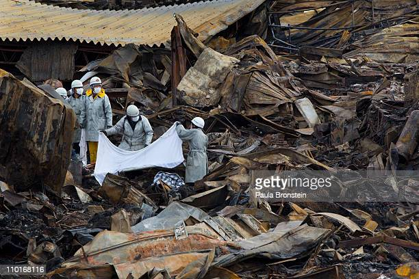 Rescue workers cover a body from the rubble of a village destroyed by the devastating earthquake fires and tsunami March 16 2011 in Kesennuma Miyagi...
