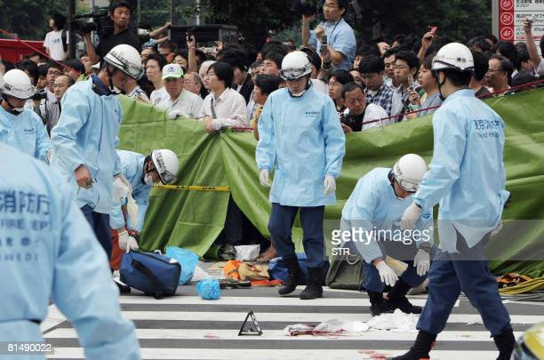 Rescue workers gather at the site where a man went on a stabbing spree in Tokyo's Akihabara electronic shops street on June 8 2008 A man Tomohiro...