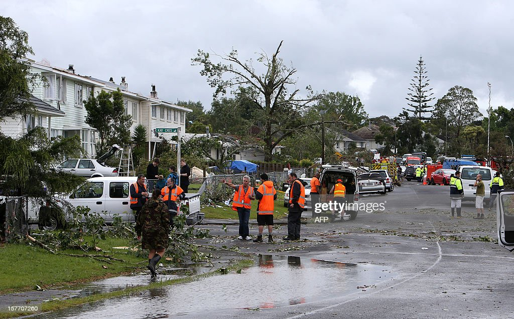 Rescue workers gather on a road amongst debris in Hobsonville, Auckland on December 6, 2012 after packed wind gusts of up to 110 kilometres (70 miles) per hour, struck suburban Hobsonville in the afternoon. A freak storm described by police as a tornado hit New Zealand's largest city Auckland on December 6 causing 'utter devastation', with three people reportedly killed in ferocious winds. AFP PHOTO / Michael Bradley