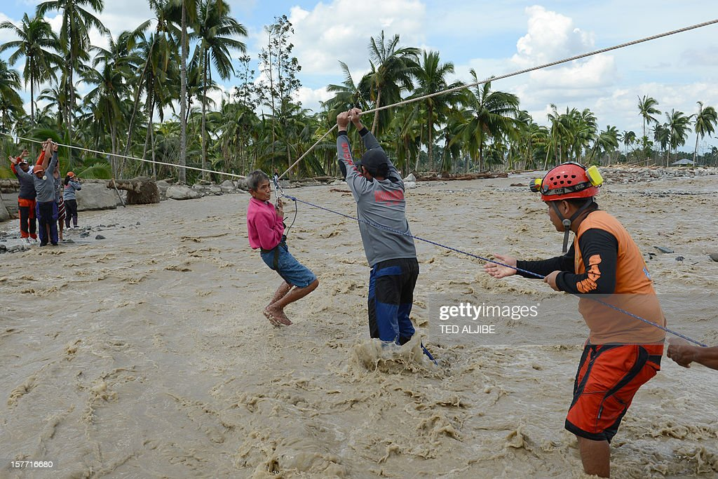Rescue workers help an elderly woman cross a surging river in New Bataan town, compostela province on December 6, 2012. Nearly 200,000 people are homeless and more than 300 dead after the Philippines suffered its worst typhoon this year, authorities said on December 6, reaching out for international aid to cope with the scale of the disaster. AFP PHOTO / TED ALJIBE