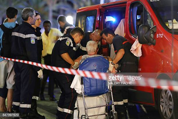 TOPSHOT Rescue workers help an injured woman to get in a ambulance on July 15 after a truck drove into a crowd watching a fireworks display in the...
