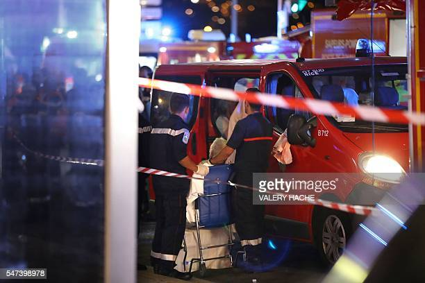 Rescue workers help an injured woman to get in a ambulance on July 15 after a truck drove into a crowd watching a fireworks display in the French...