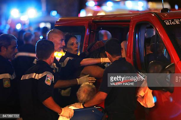 Rescue workers help injured people to get in a ambulance on July 15 after a truck drove into a crowd watching a fireworks display in the French...