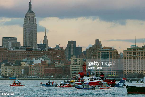 Rescue workers in boats assist a US Airways plane floating in the water after crashing into the Hudson River in the afternoon on January 15 2009 in...