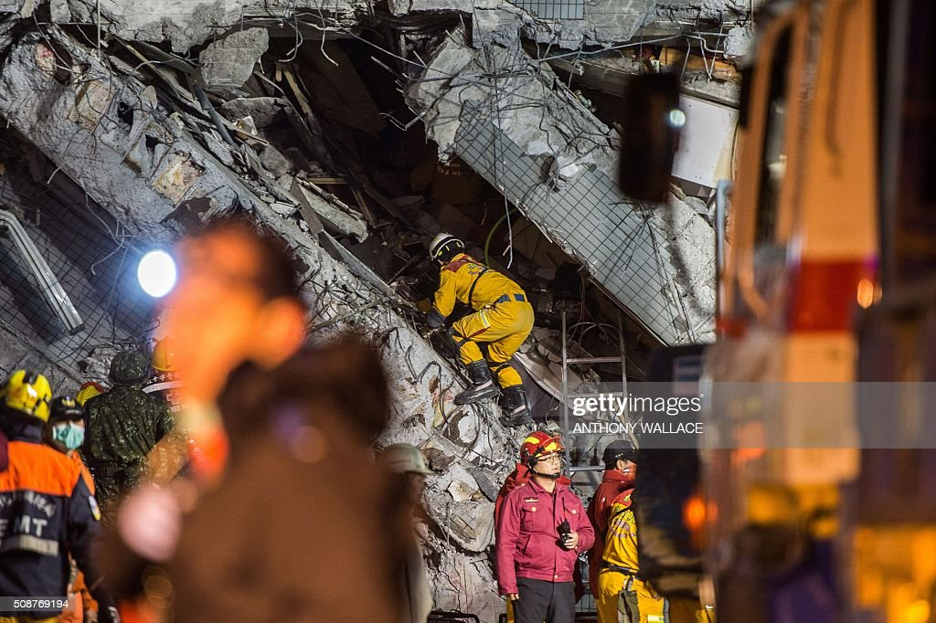 Rescue workers inspect the inside of a collapsed building in the southern Taiwanese city of Tainan following a strong 6.4-magnitude earthquake that struck early on February 6, 2016. Relatives of residents trapped in a 16-storey apartment complex felled by a powerful earthquake in Taiwan that killed 14 people were praying for miracles Saturday as rescuers sought survivors, with more than 150 missing in the quake zone. / AFP / ANTHONY WALLACE