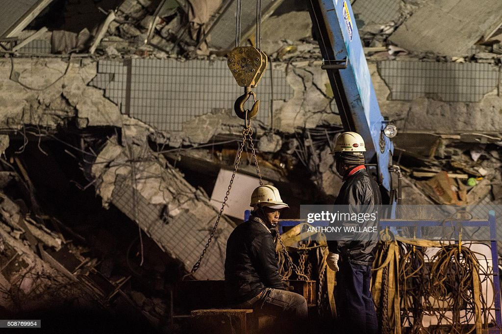 Rescue workers inspect the scene of a collapsed building in the southern Taiwanese city of Tainan following a strong 6.4-magnitude earthquake that struck early on February 6, 2016. Relatives of residents trapped in a 16-storey apartment complex felled by a powerful earthquake in Taiwan that killed 14 people were praying for miracles Saturday as rescuers sought survivors, with more than 150 missing in the quake zone. / AFP / ANTHONY WALLACE