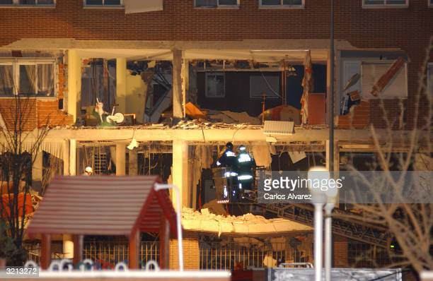 Rescue workers inspect the scene where suspects sought for the Madrid train bombings apparently set off an explosion and died when cornered by police...