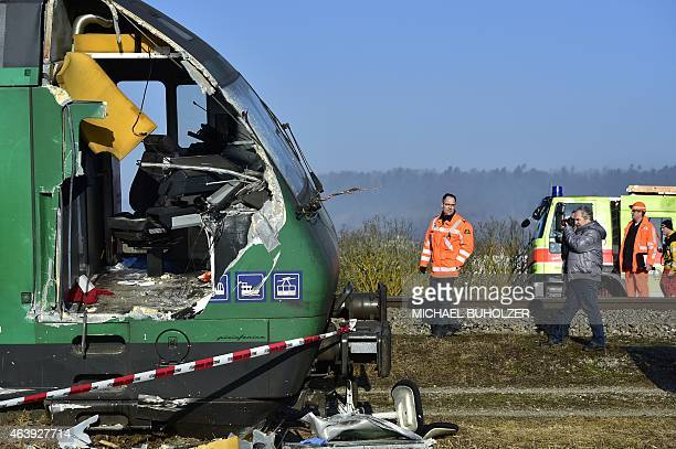 Rescue workers inspect the site of a train crash at the train station of Rafz northern Switzerland on February 20 2015 Two trains slammed into each...