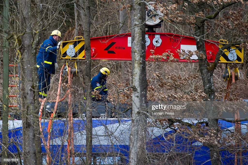 Rescue workers lift the wreckage of one of two trains that collided head-on the day before in Bavaria with a heavy duty crane on February 10, 2016 near Bad Aibling, Germany. Authorities say at least nine people are dead and over 100 injured in the collision between two trains of the Meridian local commuter train service that occurred at approximately 7:00 am yesterday.