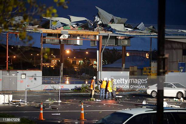 Rescue workers look at the badly damaged Albany Shopping Centre in Auckland on May 3 2011 after a freak tornado hit the area killing two people and...