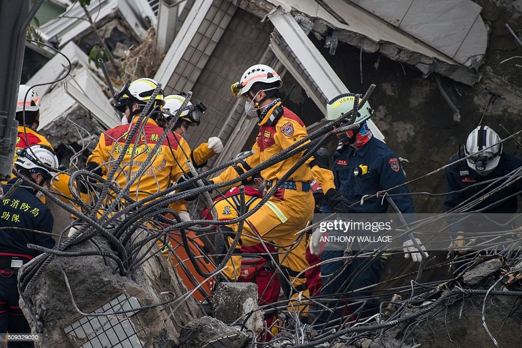 Rescue workers look for possible victims within the remains of an apartment in one of the top floors of the Wei-Kuan complex which collapsed in the 6.4-magnitude earthquake, in the southern Taiwanese city of Tainan on February 10, 2016. Taiwan prosecutors were on February 10 questioning the developer of the apartment complex that collapsed during the earthquake as prosecutors detailed flaws in construction of the building where nearly 100 people remain trapped. AFP PHOTO / ANTHONY WALLACE / AFP / ANTHONY WALLACE