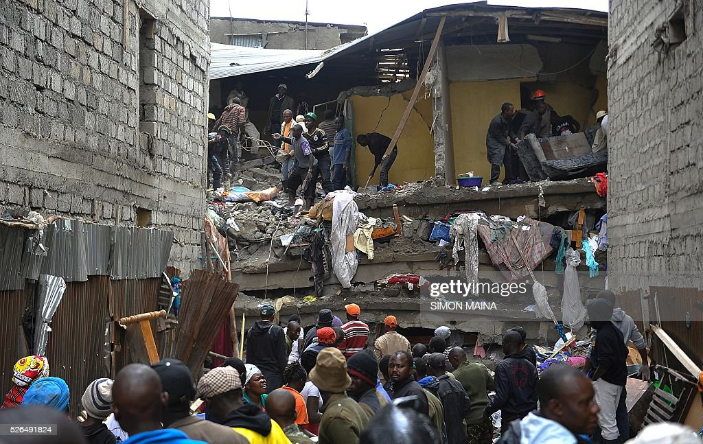 Rescue workers look for survivors after a building collapsed in Nairobi on April 30, 2016. Rescuers in the Kenyan capital made desperate efforts Saturday to free survivors including a woman and child trapped in a building that collapsed in storms that have left a total of 17 people dead. / AFP / SIMON