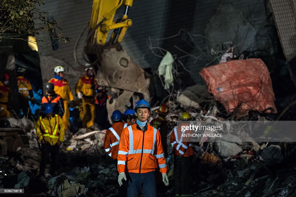 Rescue workers look for survivors and bodies after extracting rubble from the remains of a building which collapsed in the 6.4 magnitude earthquake, in the southern Taiwanese city of Tainan early on February 9, 2016. A girl aged eight and three others were rescued Monday from the rubble of a Taiwan apartment tower complex, more than two days after it was felled by an earthquake, but over 100 others remain trapped in the ruins. / AFP / ANTHONY WALLACE