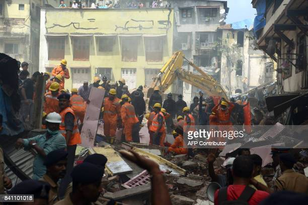 Rescue workers look for survivors at the site of a building collapse in Mumbai on August 31 2017 At least three people died and dozens were feared...