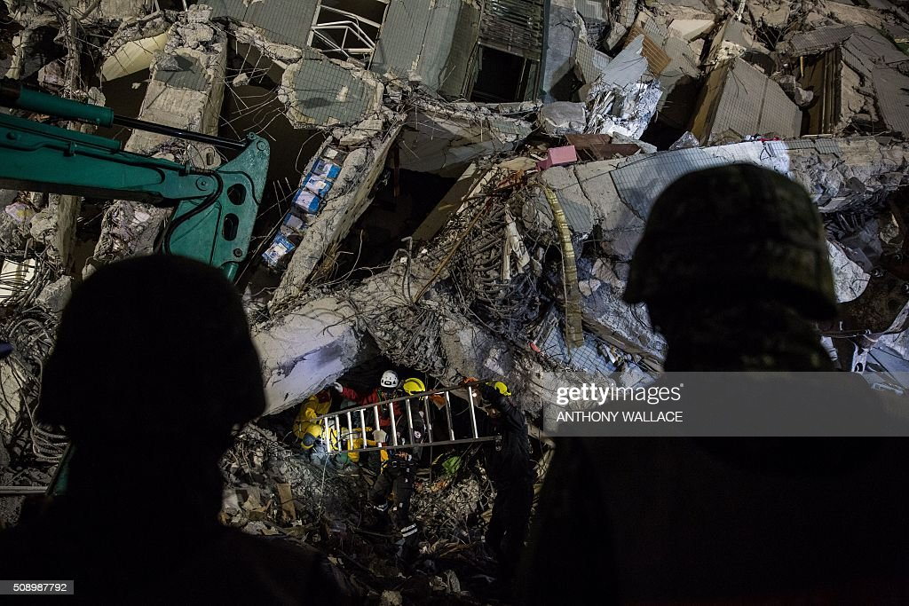 Rescue workers (C) look for survivors in the remains of a building which collapsed in the 6.4 magnitude earthquake, in the southern Taiwanese city of Tainan early on February 8, 2016. Rescuers raced on February 7 to free around 120 people buried under the rubble of an apartment complex felled by an earthquake in southern Taiwan that left 34 confirmed dead, as an investigation began into the collapse. AFP PHOTO / ANTHONY WALLACE / AFP / ANTHONY WALLACE