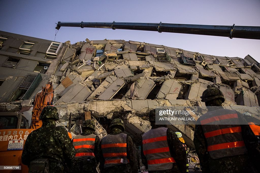 Rescue workers look for survivors in the remains of a building which collapsed in the 6.4 magnitude earthquake, in the southern Taiwanese city of Tainan on February 8, 2016. Rescuers raced on February 7 to free around 120 people buried under the rubble of an apartment complex felled by an earthquake in southern Taiwan that left 34 confirmed dead, as an investigation began into the collapse. AFP PHOTO / ANTHONY WALLACE / AFP / ANTHONY WALLACE