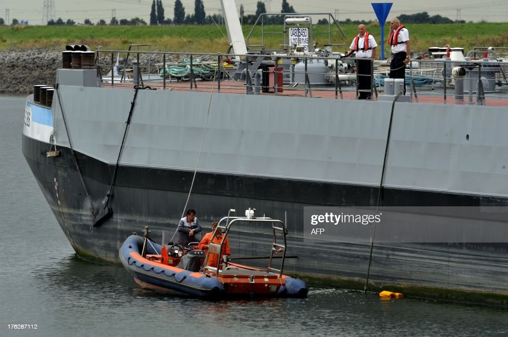 Rescue workers look for three missing people on a canal near Wemeldinge, on August 12, 2013, after a German gas tanker ploughed into a sailboat on this canal, dragging it under water. Several dive teams, helicopters, ambulances and fire engines were scrambled to the scene of the accident near Wemeldinge, around 20 kilometres (12 miles) from the Belgian border and one possible survivor was taken to hospital.