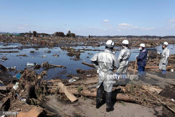 Rescue workers look over an area flooded by the tsunami on March 12 2011 in Minamisoma Fukushima Japan An earthquake measuring 89 on the Richter...