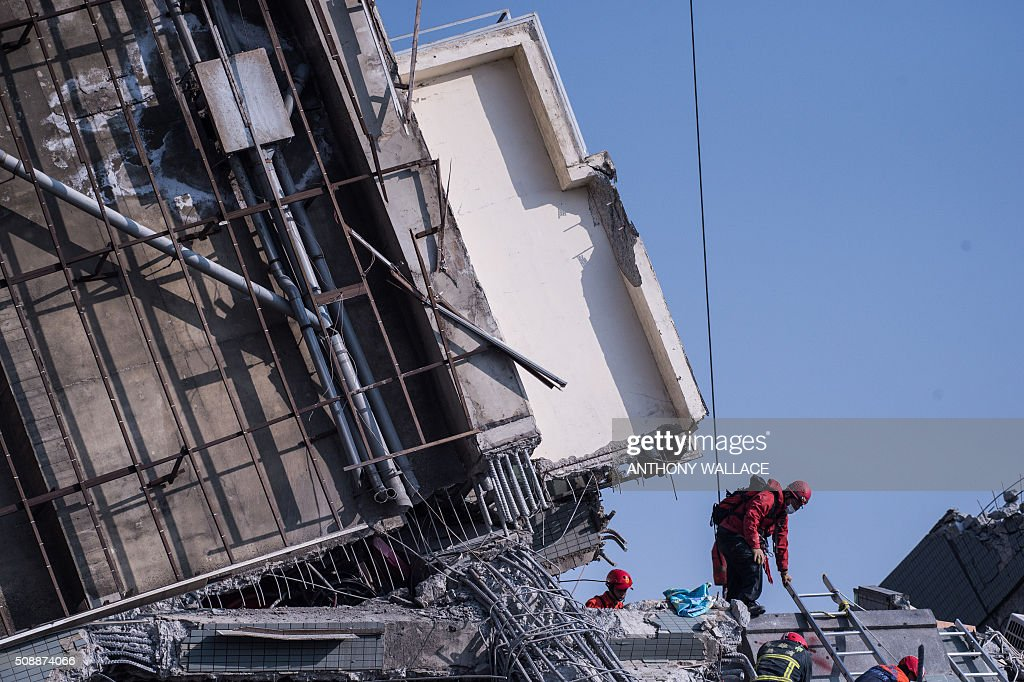 Rescue workers look through the rubble of a collapsed building in the southern Taiwanese city of Tainan on February 7, 2016, following a strong 6.4-magnitude earthquake that struck early on February 6. Rescuers raced on February 7 to free more than 120 people buried under the rubble of an apartment complex felled by an earthquake in southern Taiwan that left 24 confirmed dead, as an investigation began into the collapse. AFP PHOTO / ANTHONY WALLACE / AFP / ANTHONY WALLACE