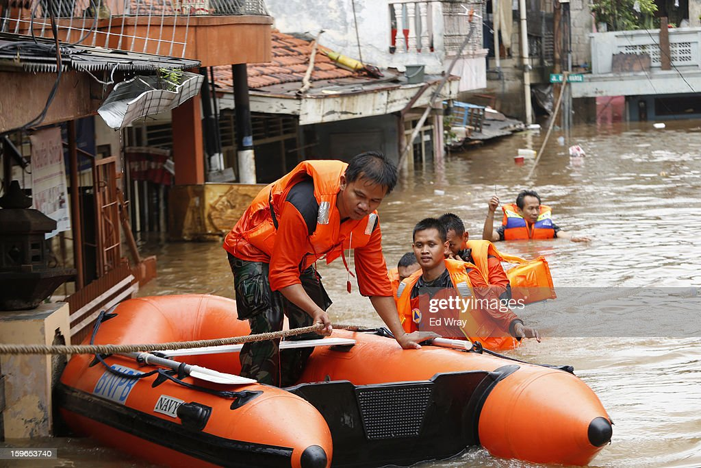 Rescue workers manouver a boat in a flooded area on January 18, 2013 in Jakarta, Indonesia. According to the National Disaster Management Agency, about 50 percent of the capital is under water following the floods which have so far claimed eleven lives and displaced thousands of Indonesians.