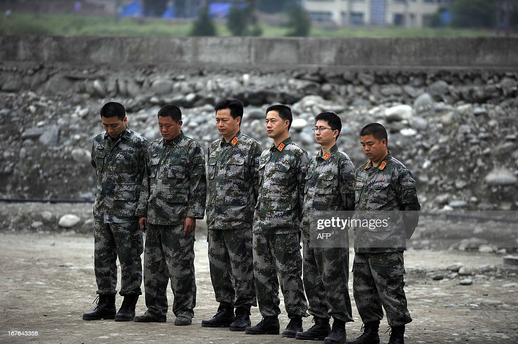 Rescue workers mourn earthquake victims in Lingguan township of Baoxing county in Yaan, southwest China's Sichuan province on April 27, 2013. China's southwestern Sichuan province stopped on April 27 to mourn the victims of a deadly earthquake that struck exactly a week ago, state media reported. CHINA