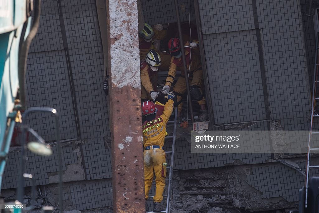 Rescue workers pass objects down to a colleague at the site of a collapsed building in the southern Taiwanese city of Tainan on February 7, 2016, following a strong 6.4-magnitude earthquake that struck early on February 6. Rescuers raced on February 7 to free more than 120 people buried under the rubble of an apartment complex felled by an earthquake in southern Taiwan that left 24 confirmed dead, as an investigation began into the collapse. AFP PHOTO / ANTHONY WALLACE / AFP / ANTHONY WALLACE