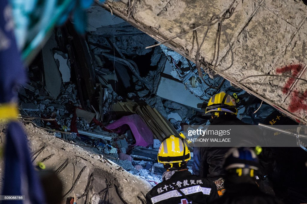Rescue workers prepare to enter the remains of a flat during their search and rescue operation in a building which collapsed in the 6.4 magnitude earthquake, in the southern Taiwanese city of Tainan early on February 9, 2016. Rescuers are set to start using diggers and extractors to remove giant concrete slabs once they have ensured all residents from the upper parts of the rubble have been freed. AFP PHOTO / ANTHONY WALLACE / AFP / ANTHONY WALLACE
