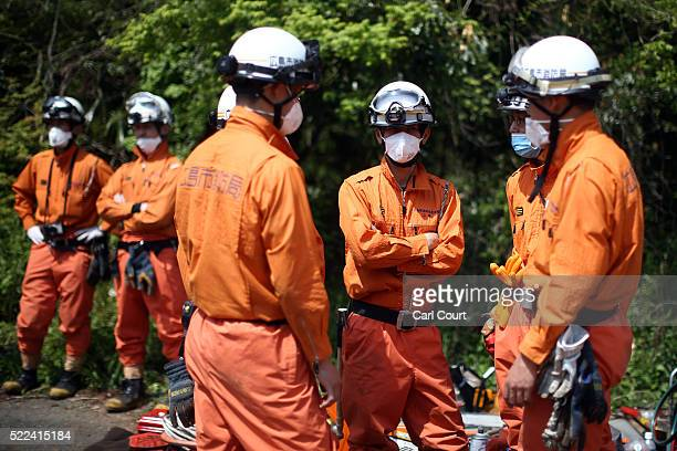Rescue workers prepare to search the area around houses that were destroyed by a landslide following an earthquake on April 19 2016 in Minamiaso near...