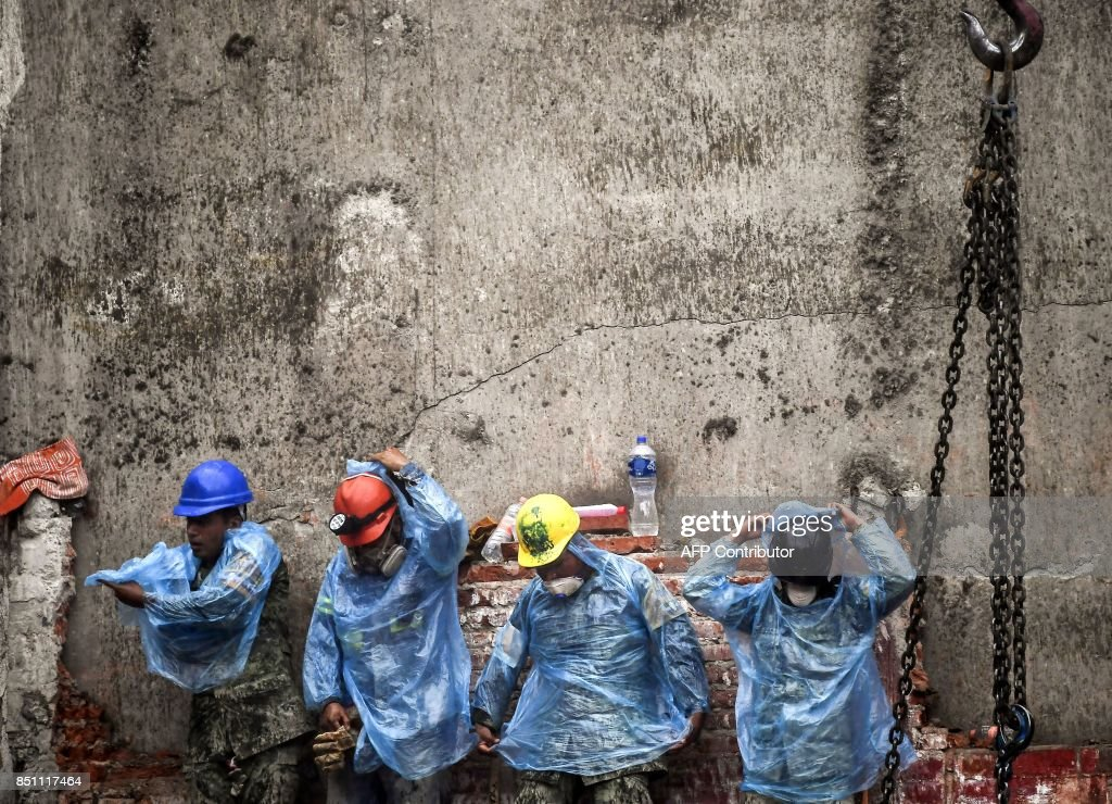 TOPSHOT - Rescue workers put on rain gear during the search for survivors and bodies in Mexico City on September 21, 2017, two days after a strong quake hit central Mexico. A powerful 7.1 earthquake shook Mexico City on Tuesday, causing panic among the megalopolis' 20 million inhabitants on the 32nd anniversary of a devastating 1985 quake. /