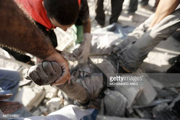 Rescue workers remove the body of a man after digging him up from under the rubble of his home following an Israeli air strike on Beit Hanun in the...