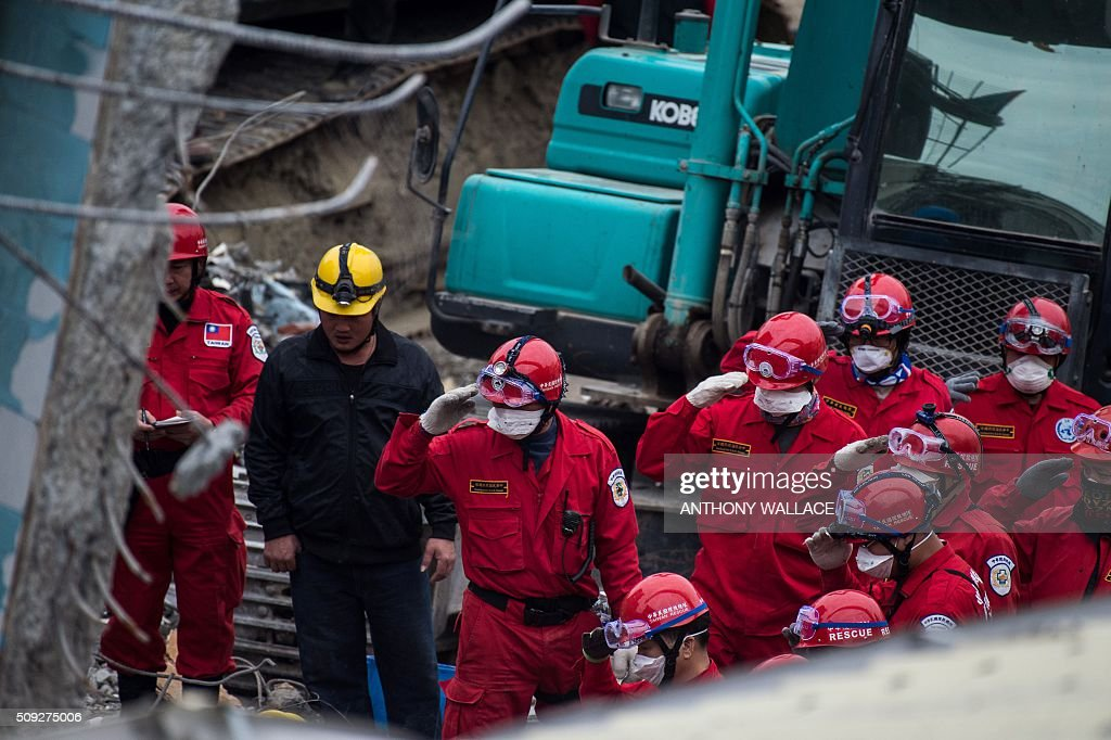 Rescue workers salute before extracting the body of a male student, who was thought to be alive but died before being rescued from the remains of the Wei-Kuan complex which collapsed in the 6.4 magnitude earthquake, in the southern Taiwanese city of Tainan on February 10, 2016. The developer of a Taiwan apartment complex that collapsed during a strong earthquake was arrested February 9, as rescuers reported hearing signs of life in the rubble where some 100 people are still trapped. AFP PHOTO / ANTHONY WALLACE / AFP / ANTHONY WALLACE