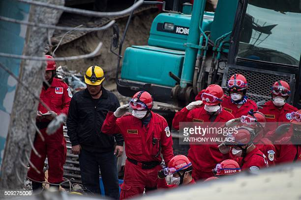 Rescue workers salute before extracting the body of a male student who was thought to be alive but died before being rescued from the remains of the...