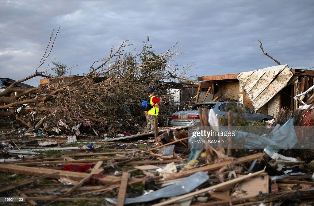 A rescue workers search amonst debris of a tornado-devastated home on late May 21, 2013 in Moore, Oklahoma. Families returned to a blasted moonscape that had been an American suburb Tuesday after a monstrous tornado tore through the outskirts of Oklahoma City, killing at least 24 people. Nine children were among the dead and entire neighborhoods vanished, with often the foundations being the only thing left of what used to be houses and cars tossed like toys and heaped in big piles. AFP PHOTO/Jewel Samad