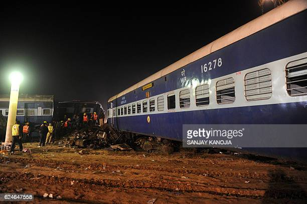 Rescue workers search for survivors in the wreckage of a derailed train near Pukhrayan in Kanpur district on November 20 2016 Emergency workers raced...