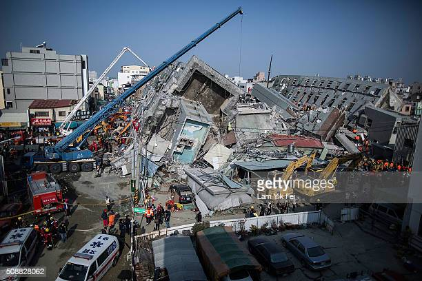 Rescue workers search for victim at a collapsed building on February 7 2016 in Tainan Taiwan A magnitude 64 earthquake hit southern Taiwan early...