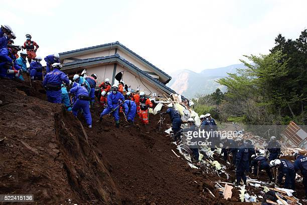 Rescue workers search the area around a house that was destroyed by a mudslide following an earthquake on April 19 2016 in Minamiaso near Kumamoto...