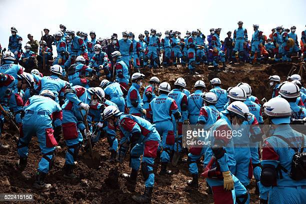 Rescue workers search the area around houses that were destroyed by a landslide following an earthquake on April 19 2016 in Minamiaso near Kumamoto...