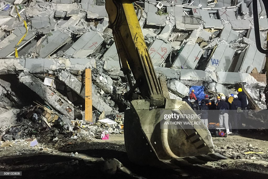 Rescue workers (R) search through rubbles for belongings for relatives to help identify from the remains of a building which collapsed in the 6.4 magnitude earthquake, in the southern Taiwanese city of Tainan early on February 9, 2016. Rescuers deployed heavy machinery on February 9 in a renewed effort to locate more than 100 people trapped in the rubble of a Taiwan apartment complex felled by an earthquake as the 72-hour 'golden window' for finding survivors passed. AFP PHOTO / ANTHONY WALLACE / AFP / ANTHONY WALLACE