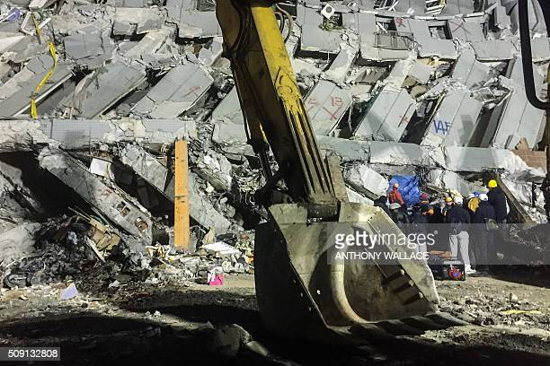Rescue workers search through rubble for belongings for relatives to help identify from the remains of a building which collapsed in the 64 magnitude...