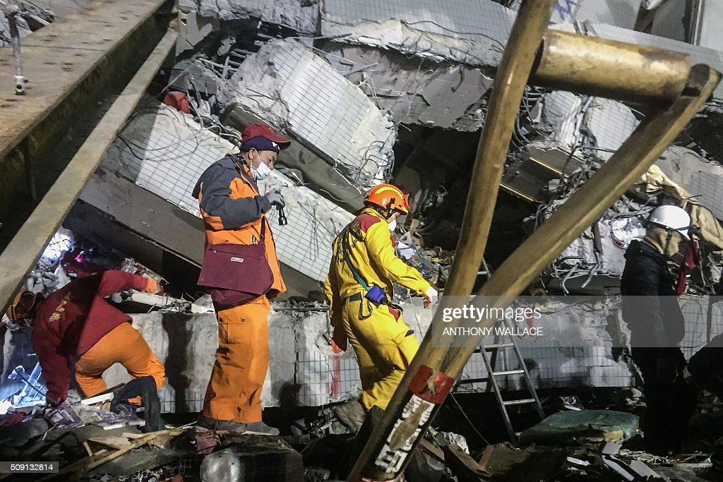 Rescue workers search through rubbles for belongings for relatives to help identify from the remains of a building which collapsed in the 6.4 magnitude earthquake, in the southern Taiwanese city of Tainan early on February 9, 2016. Rescuers deployed heavy machinery on February 9 in a renewed effort to locate more than 100 people trapped in the rubble of a Taiwan apartment complex felled by an earthquake as the 72-hour 'golden window' for finding survivors passed. AFP PHOTO / ANTHONY WALLACE / AFP / ANTHONY WALLACE