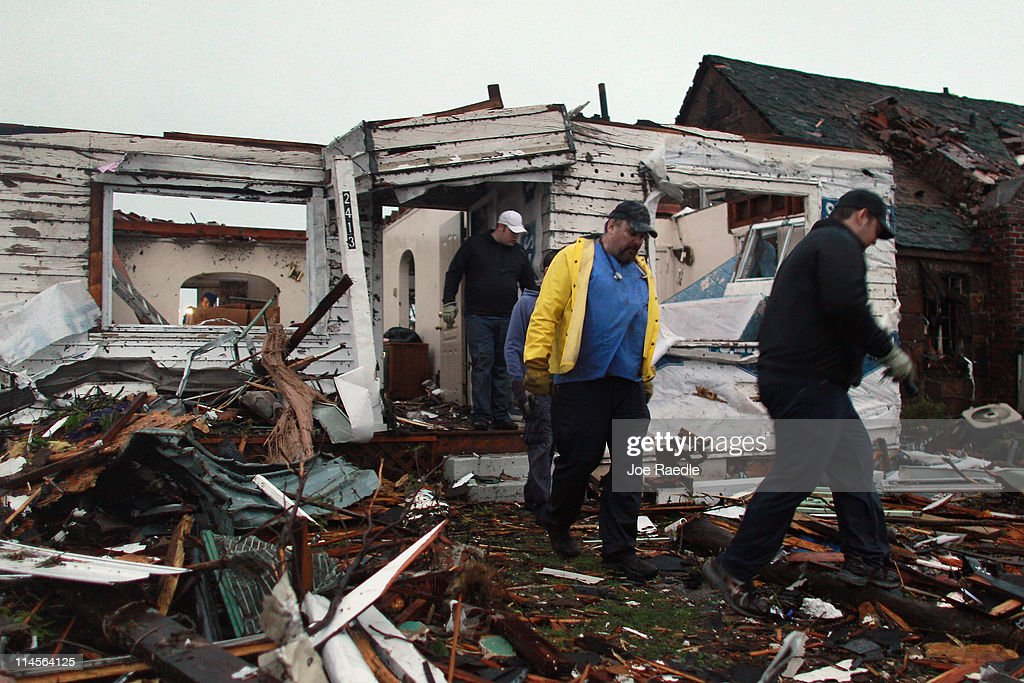 Rescue workers search through the debris of a home after116 people where killed when a massive tornado passed through the town on May 23 2011 in...