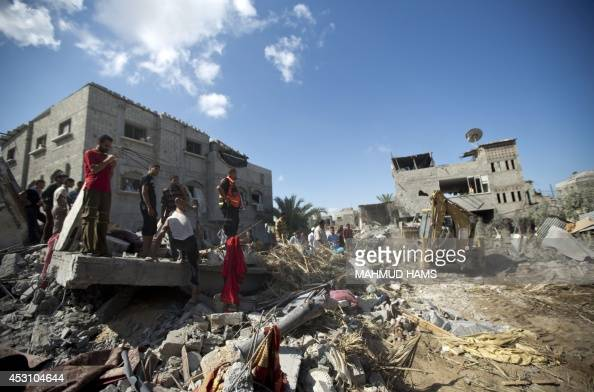 Rescue workers search through the rubble of a house hit by an Israeli military strike that killed at least five members of alKhattab family in Deir...