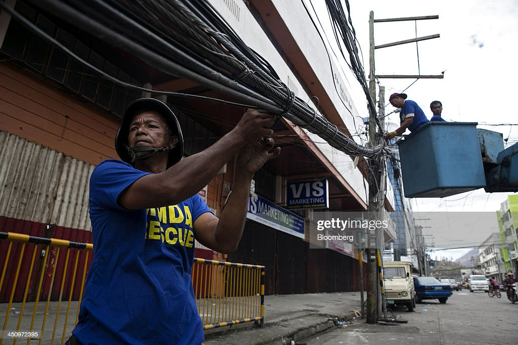 Rescue workers secure downed power lines in downtown Tacloban, the Philippines, on Monday, Nov. 18, 2013. Super Typhoon Haiyan slammed into the central Philippines on Nov. 8, knocking down most buildings, killing thousands, displacing 4 million people and affecting more than 10 million. Photographer: Paula Bronstein/Bloomberg via Getty Images
