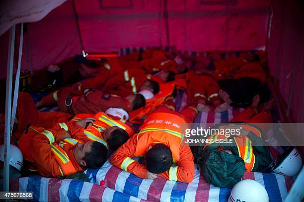Rescue workers sleep in a tent near the scene of the capsized passenger ship Dongfangzhixing or 'Eastern Star' in the Yangtze river at Jianli in...