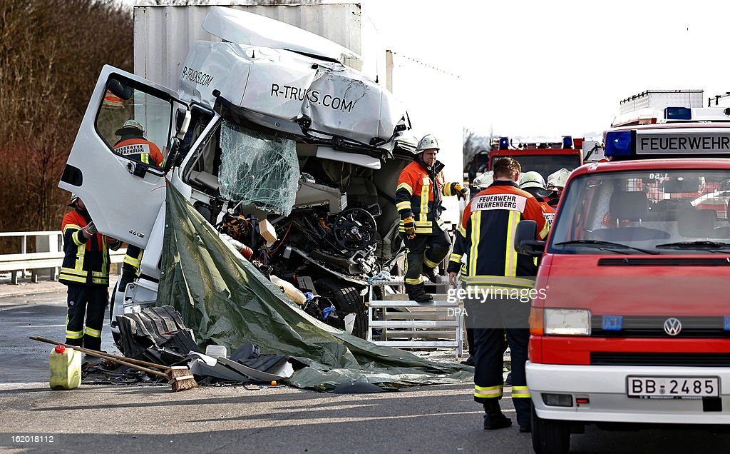 Rescue workers stand at a destroyed truck at a scene of an accident on a motorway near Singen, southern Germany, on February 18, 2013. AFP PHOTO / Thomas Niedermueller GERMANY OUT