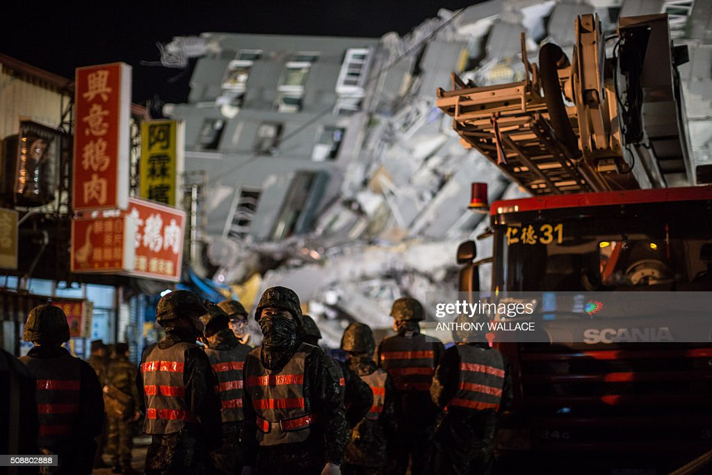 Rescue workers stand at the scene of a collapsed building (back) early on February 7, 2016 following a strong 6.4-magnitude earthquake on February 6. Rescuers raced against time on February 7 to free more than 100 people still buried beneath the rubble of apartment blocks felled by the powerful earthquake in southern Taiwan that left 18 dead. AFP PHOTO / ANTHONY WALLACE / AFP / ANTHONY WALLACE