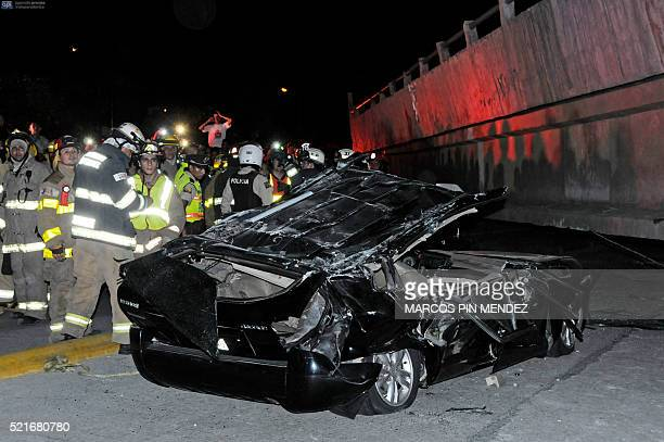TOPSHOT Rescue workers stand before a destroyed car after the collapse of a bridge in an earthquake April 16 2016 in Guayaquil Ecuador At least 28...