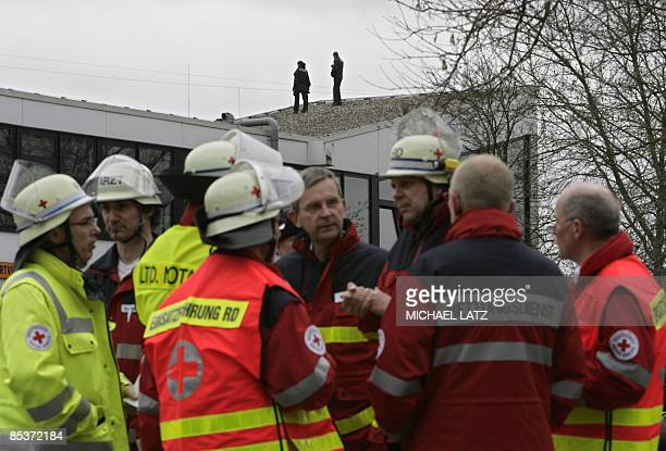 Rescue workers stand in front of the Albertville Realschule secondary school in Winnenden southern Germany where a shooting took place on March 11...